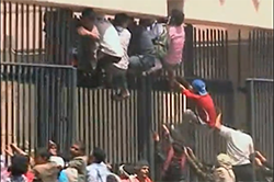 Protestors attempt to scale the gate of the US embassy in Yemen.