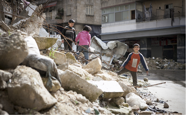 One of the countless bombed residential buildings in Aleppo, Syria. Three children collect firewood amongst the rubble. © Richard Harvey | dreamstime.com