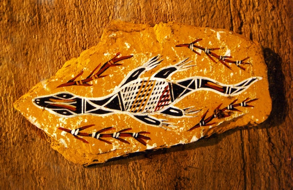 An image of a piece of abstract Australian aboriginal art, a swimming lizard or crocodile with patterned back, surrounded by water weeds, painted on wood. A beautiful and quaint sample of traditional native aborigine arts, from down under. © Joanne Zh | Dreamstime.com