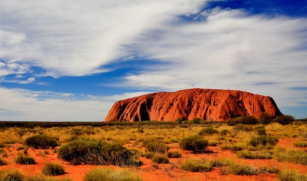 A panorama of Australia's famous monolith, Uluru (Ayers Rock), showing the vivid change in color as the sun goes down. Uluru – Kata Tjuta National Park, Northern Territory, Australia. © Stanislav Fosenbauer | Shutterstock.com