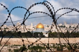 A view of the Old City of Jerusalem, including the Dome of the Rock through coils of razor wire, illustrating the Holy Land's history of division and conflict. © Ryan Rodrick Beiler | Shutterstock