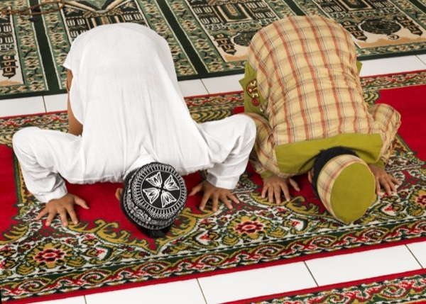 Muslim children praying in a mosque. © Distinctive Images | shutterstock.com