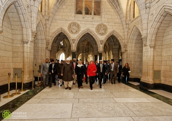 His Holiness walks through the halls of Parliament accompanied by MP Judy Sgro and other guests. © Makhzan-e-Tasaweer