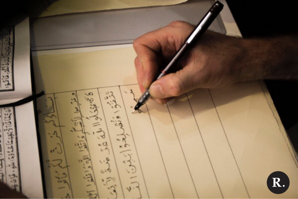 A person writes a verse of the Qur'an for the Al-Qalam Project